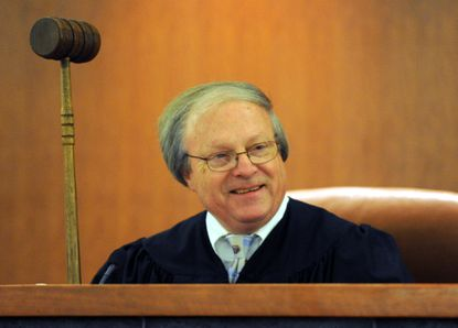 Judge Ronald Silkworth holds up his special gavel he uses on National Adoption Day. The Circuit Court for Anne Arundel County commemorates National Adoption Day on Thursday, with Judge Ronald Silkworth signing the papers to make the adoptions legal and a reception afterwards. He will retire Aug. 27.