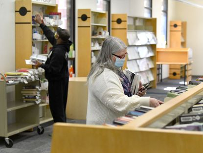 Jo-Ann Baker of Aberdeen, right, searches for a title among the shelves of books as fellow library patron Abu Acheneje finds his selection during their visit to the Aberdeen library Tuesday, March 2021. The Aberdeen library branch is one of the few that has officially reopened with some restrictions as of Monday, March 8, 2021.