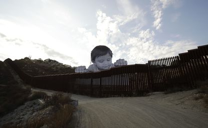 A mural in Tecate, Mexico, sits just beyond the U.S.-Mexico border fence, on Sept. 8, 2017, as seen from Tecate, Calif. A French artist aiming to prompt discussions about immigration erected the 65-foot-tall cut-out photo.