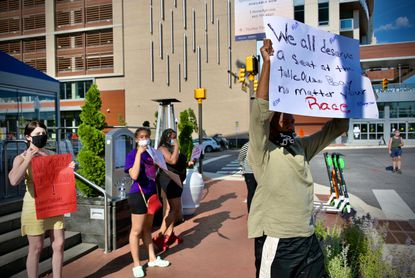Protesters chant decrying racism at the entrance of Ouzo Bay restaurant at Harbor East. June 24, 2020