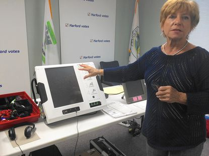 Dale Livingston, deputy director of the Harford County Board of Elections, shows a new ExpressVotes machine that will be used during early voting.