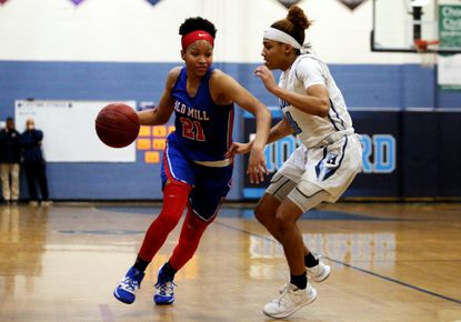 Old Mills' Deja Atkinson (21) in action against Howard's Anii Harris (4) during a girls high school playoff basketball match between Howard and Old Mill in this March photo.