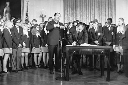 """FILE - In this July 4, 1971 file photo, President Richard Nixon signs the Constitution's newest amendment which guarantees 18-year-olds the right to vote in all elections. Robert Kunzig, general services administrator, waits to certify officially ratification of the 26th amendment. The signing took place in East Room of the White House in Washington. Paul Larimer of Concord, Calif. , a member of the singing group """"Young Americans"""" also signed the amendment."""
