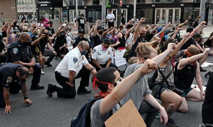 In June 2020, Baltimore City Police Commissioner Michael Harrison (white shirt, center) and officers took a knee with protestors to remember George Floyd's struggle under the knee of former Minneapolis police officer Derek Chauvin.