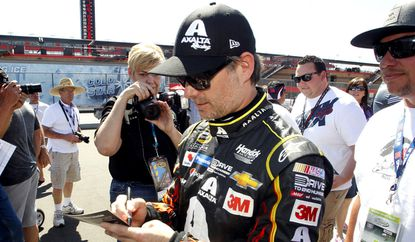 Jeff Gordon signs an autograph for a fan after a practice session to qualify for Sunday's NASCAR Sprint Cup Series auto race in Fontana on Friday.