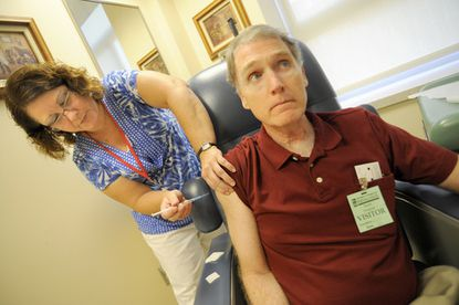 Linda Wadsworth, a registered nurse, gives study volunteer Richard Messick, 58, of Baltimore an injection of the H1N1 test vaccine at the University of Maryland's School of Medicine's Center for Vaccine Development.