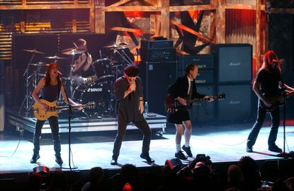 """Rockers AC/DC perform their hit, """"Highway to Hell,"""" as they were inducted into the Class of 2003 during the Rock and Roll Hall of Fame's 18th annual induction dinner at the Waldorf-Astoria in New York, New York. (Richard Corkery/New York Daily News)."""