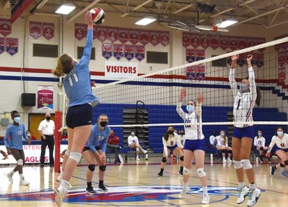 Howard's #11, Anna Plecas spikes the ball over the net and Centennial defenders, #10, Emily Hollwedel, and #1, Mailihn Godschall in the 2nd game. Volleyball match between Howard and Centennial at Centennial High School Wednesday March 17, 2021. Howard won the match 2 games to 0.