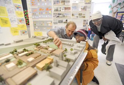 Jonathan Marvel, left, of Rogers Marvel Architects, explains his firm's design for a new public school planned for the East Baltimore Development Inc. renewal area to Ryheem Brown, 7, of Baltimore and his great-grandmother Joyce Bess, right, during an open house at East Baltimore Community School. File. (Steve Ruark/Special to The Baltimore Sun).