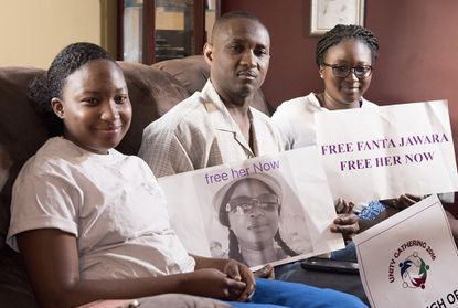 In this June 14, 2015, file photo, Ebrima Jawara poses with his daughters Sarah, left, and Aminata, while holding a picture of his wife Fanta Darboe Jawara.