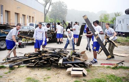 Students, faculty and volunteers from Ripken Baseball load what was once a fence onto a trailer to be hauled away Friday morning at Aberdeen High School, as part of clean-up project sponsored by the Ripken Outreach and Community Service organization.