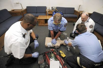 (From left) Capt. Louis Winston, Master firefighter John Poole, Capt. Dale Becker and firefighter Chad Fronteras demonstrate a resuscitation technique on a dummy at Howard County fire station 8 on Frederick Road. They'll be training personnel from other stations.