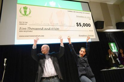 Competition host Jason Stambaugh, left, and Caroll Biz Challenge winner Dawn Pritchard, right. celebrate Pritchard's win by holding up a $5,000 check at McDaniel College in Westminster.