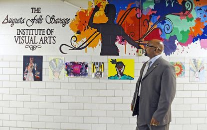 Lionel F. Jackson Jr., principal of Augusta Fells Savage Institute of Visual Arts, observes student artwork at the Baltimore school, one of seven city schools targeted for turnaround efforts under a federal school improvement program in 2019. (Kenneth K. Lam/Baltimore Sun).