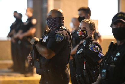 Baltimore police officers wearing face masks while keeping an eye on demonstrators as they continue to protest the dewath of George Floyd.