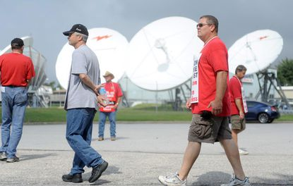 Striking Verizon workers walk the picket line outside a company facility in Laurel.