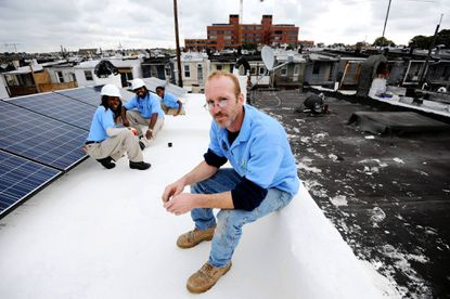 Ed Sheeks, project leader with Civic Works, sits on a cool roof he and a crew installed. Also from CIvic Works are left, front to back, Crystal Hudson, James Simpson, and Daysha Bragg.