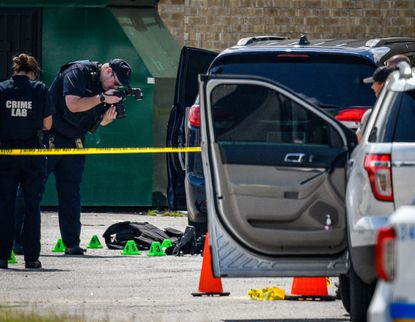 A crime lab technician takes photos of body armor and evidence markers in the Security Square Mall parking lot where a suspect was fatally shot by police after he shot and injured two Baltimore officers who were attempting to arrest him on a warrant related to a homicide in the city.