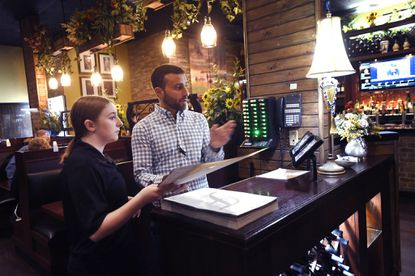 dylanGeorge Sakellis, owner of Fratelli's Italian and Seafood restaurant, helps Kaitlyn Owen as she seats tables at the restaurant's Hampstead location Friday, June 11, 2021.
