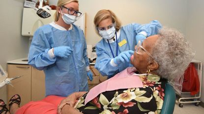 Annie Isaacs, pre-doctoral dental student, left, watches as Dr. Adila Baig (cq), faculty in the department of special care and geriatrics, oversees Isaacs' denture work for patient Arletha Chapman, 86, from Bowie.