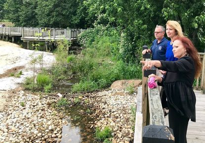 """Stephanie Noye, MS4 permit coordinator for the City of Havre de Grace, shows Maryland Commerce Secretary Kelly Schulz some city stormwater management projects near the promenade in this June 2019 file photo. City Director of Administration Patrick Sypolt is with them. Havre de Grace is seeking state and federal permits to redevelop riverfront lots the city owns along Water Street as a """"living shoreline,"""" with native plants and a system to filter stormwater runoff, according to a presentation from Noy earlier this week."""
