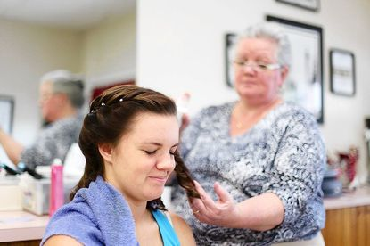 Kathie Nilsen, right, puts the finishing touches on her daughter, Bridget's, hair as the Catonsville High School sophomore got her hair styled at Kathie's Hair M salon for the Catonsville High School junior prom May 5.