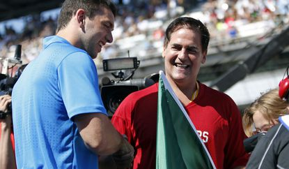 Indianapolis Colts quarterback Andrew Luck, left, presents Dallas Mavericks owner Mark Cuban with the green flag that he'll use as honorary starter for the Indy 500 on Sunday.