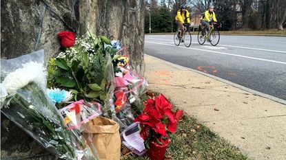 A pair of cyclists pass by a memorial on Roland Ave at the site where cyclist Thomas Palermo was struck and killed Dec. 27.