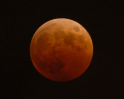 A full lunar eclipse tints the moon a reddish hue at 9:14 p.m. on Oct. 27, 2004