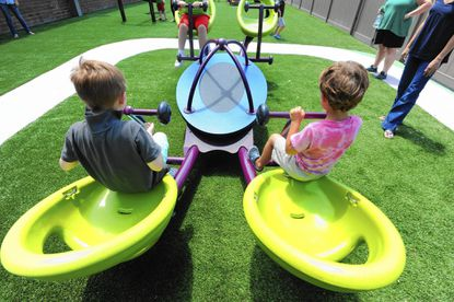Children use the We-Saw, made for 4 people, at The Shafer Center, a center for autistic children, which recently installed new therapeutic playground equipment designed to help children with motor skills and socialization.