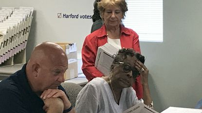Carol Bruce, seated, a member of the Harford County Board of Elections, looks over a provisional ballot at the election board headquarters in July. Director Kevin Keene, left, and Dale Livingston, standing, deputy director of elections, were put on administrative leave Oct. 31.