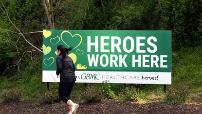 """A woman runs by a """"Heroes Work Here"""" sign outside the Greater Baltimore Medical Center entrance. April 16, 2020"""