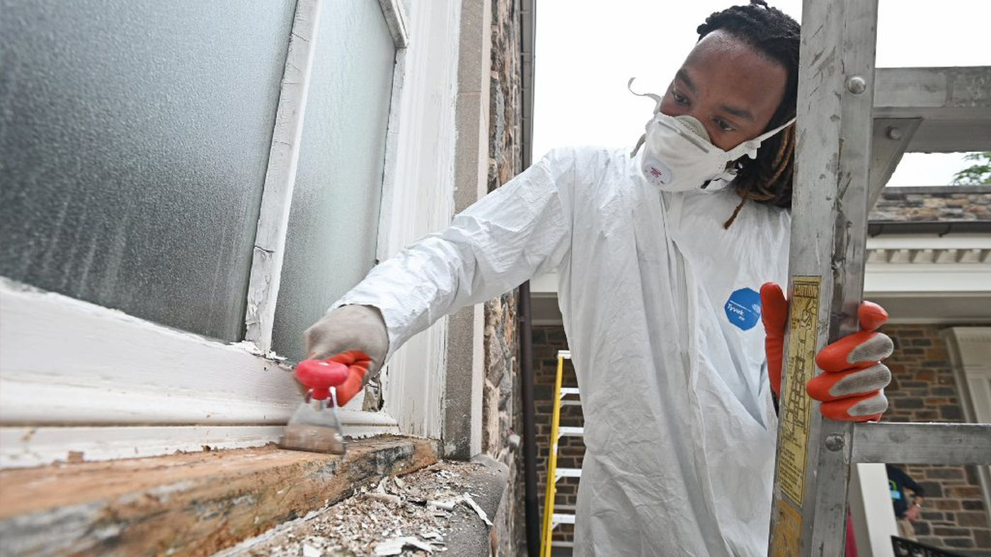 Charleus scrapes lead paint off of a window frame at the Morgan State University Memorial Chapel Thursday as part of the Touching History program.