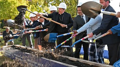 Archbishop William Lori (center) and other dignitaries participate in a ceremonial groundbreaking for the Mother Mary Lange Catholic School at the 700 block of West Lexington Street in Baltimore.