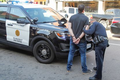 San Diego police officer Mike Martinez pulls over, tickets and detains a man who was using his cell phone while driving last April in San Diego, California. A crackdown on distracted driving might be a more effective way to reduce pedestrian deaths than lowering speed limits.