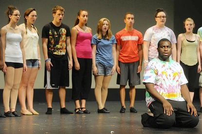 "Sola Fadiran, a rising junior at Glenelg High School, is surrounded by other cast members during a rehearsal of ""Children of Eden."""