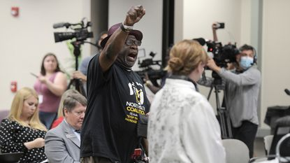 """In this June 10, 2021, file photo, Ben Frazier, the founder of the Northside Coalition of Jacksonville, Florida chants """"Allow teachers to teach the truth"""" at the end of his public comments opposing the state of Florida's plans to ban the teaching of critical race theory in public schools. Local school boards around the country are increasingly becoming cauldrons of anger and political division, boiling with disputes over such issues as COVID-19 mask rules, the treatment of transgender students and how to teach the history of racism and slavery in America. (Bob Self/The Florida Times-Union via AP, File)"""
