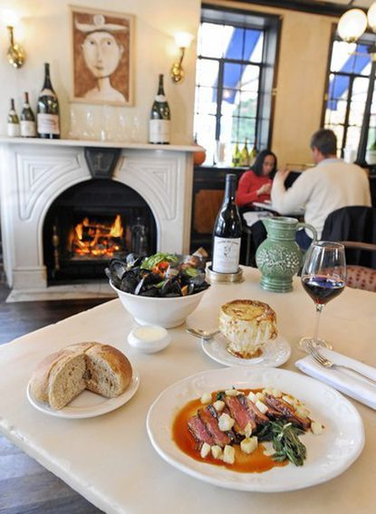 Pictured Petit Louis dishes are Magret de Canard Roti (duck breast, Swiss chard and grilled pears) bottom, Soupe a L'oignon Gratinee (Louis's Famous Onion Soup) middle, and Moules a la Provencale (sauteed mussels, tomato, white wine, garlic, basil) top.