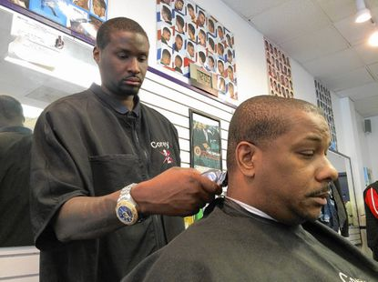Corey Samuel, left, cuts the hair of Columbia resident Kenneth Phillips inside Community Cutz Barber Shop and Salon located in the Long Reach Village Center. Both Samuel and Phillips noted the decline in the center, and added they have hope for a county purchase.