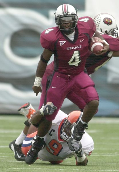 Temple University runningback Tanardo Sharps, top, breaks a tackle by Syracuse's Clifton Smith, bottom, during the first half Saturday, Oct. 12, 2002 in Philadelphia. (AP Photo/Chris Gardner)