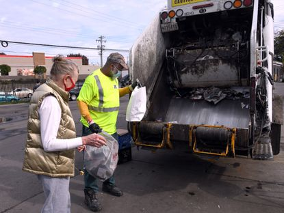 Sandy Sause, left, who lives in Hampden, drops off her recycling Oct. 28, 2020, at a Baltimore City recycling facility on Sisson Street. George McLee, right, a bureau of solid waste driver, helps with the items.