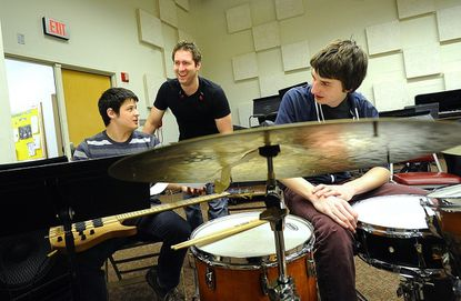 Adam Silverman, center, looks over sheet music with bassist Paul Morales, left, and Sean Durkin during a visit to McDaniel College's Jazz Ensemble in Westminster Monday. Silverman, a 2003 McDaniel graduate, now works as a touring drummer for country musician Lauren Alaina.