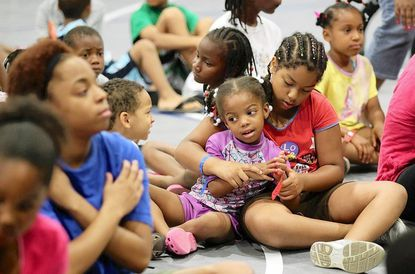 Samaira Hammond, center, 4, sits with Mira Ghersi, right, 9, in the multi-purpose room (which doubles as the church sanctuary) during Celebration Church's summer camp. Church leaders wanted to create a welcoming environment for Long Reach youths.