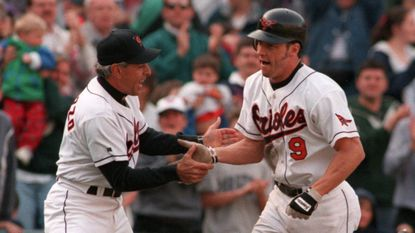 Orioles center fielder Brady Anderson, right, is congratulated by third base coach Sam Perlozzo after homering to right with one out in the ninth against right-hander Pat Mahomes to beat Minnesota on April 13, 1996. It was Anderson's third homer of 1996; he finishes with 50.