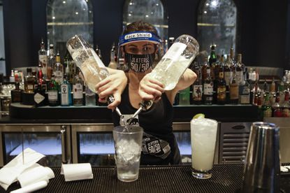 A bartender mixes a drink while wearing a mask and face shield at Slater's 50/50 on July 1, 2020, in Santa Clarita, Calif.