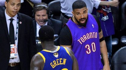 Rapper Drake, right, says something to Golden State Warriors forward Draymond Green (23) after the Toronto Raptors defeated the Warriors in Game 1 of basketball's NBA Finals, Thursday, May 30, 2019, in Toronto.