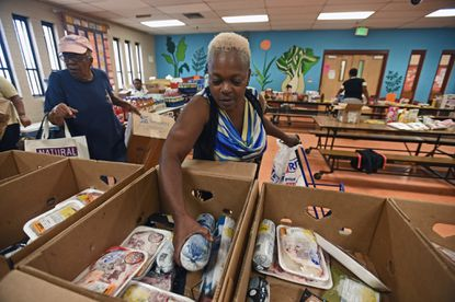 Sharon Geathers, center, and Faith Anderson, left, pick out grocery items from the food pantry at Calvin Rodwell Elementary school. This is the first food handout for this school year. Staff and volunteers at Calvin Rodwell Elementary hand out over 4000 pounds of grocery items to families of students and from the community. Food pantry program is a big part of the community school model. Kenneth K. Lam/Baltimore Sun DSC_2778 md-community-schools lam