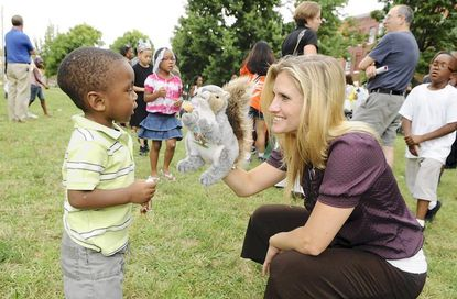 Brooke Poklemba, right, with the Baltimore Child Abuse Center, entertains 2 year old Noah Campbell of Charles Village with a squirrel hand puppet during a National Night Out event on 23rd Street and Calvert Street in Baltimore on Tuesday. National Night Out, celebrating its 28th year, is a drug and crime prevention event with participating communities all across America.