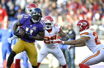 Ravens wide receiver Kamar Aiken (11) runs past Kansas City Chiefs defenders for a touchdown in the first half.