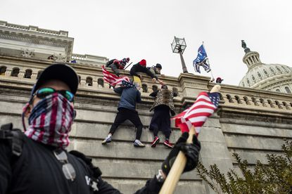 Supporters of President Donald Trump scale a wall on the Senate side of the Capitol Building in an attempt to disrupt the certification of the Electoral College results, Jan. 6, 2021. Poor planning among a constellation of government agencies and a restive crowd encouraged by President Trump set the stage for the unthinkable.